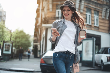 Smiling young girl in trendy hat is holding smartphone and cup of hot drink. She is using earphones while walking in the street and looking at mobile