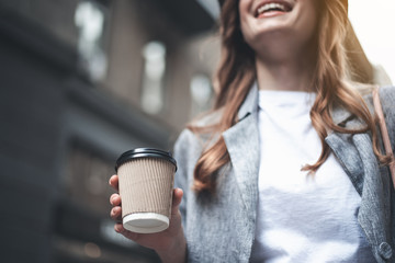 Low angle close up of female hand holding hot drink outside. Lady is standing and smiling somewhere outdoors