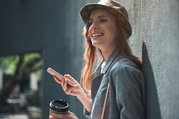 Cheerful young woman holding phone and hot drink. She is standing outside in trendy hat and leaning against wall.