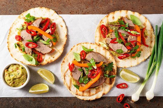 Mexican tacos with roasted  duck  meat, vegetables and green onion. Top view