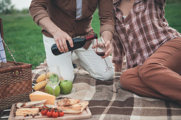 Printed kitchen splashbacks Picnic Close up of man arm pouring red wine from bottle into glass. Woman is sitting near husband on the blanket and relaxing. Romantic picnic on grass field concept