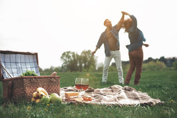 Carefree middle-aged man and woman are moving in rhythm of music in the nature. Focus on picnic basket and food with wineglasses on grass