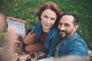 Lets remember every happy moment together. Top view portrait of joyful husband and wife are taking photo of themselves while having picnic in the nature. Man is stretching hand up and embracing woman