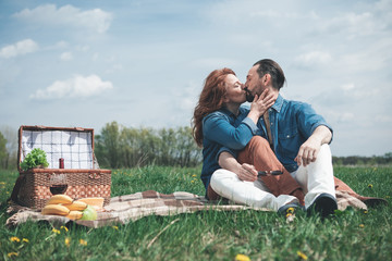 Affectionate couple is kissing while relaxing in the nature together. Their eyes are closed with love and passion