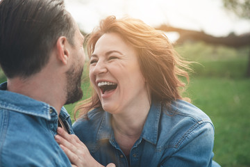 Portrait of excited middle-aged woman is laughing from the joke which man telling her. They are relaxing in the nature and hugging