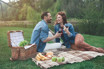 Lets drink for us. Happy loving couple is having picnic in the nature. They are holding wineglasses and smiling while sitting on blanket