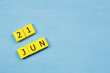 JUN 21, yellow cube calendar on blue wooden surface with copy space