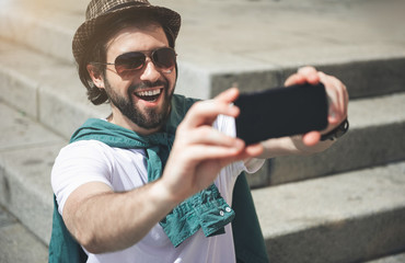 Positive picture. Portrait of content guy full of impressions of walking around the city. He is making selfie on smartphone. Focus on face
