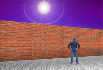 Man is standing in front of a long brick wall. The concept of obstacles in achieving your dreams