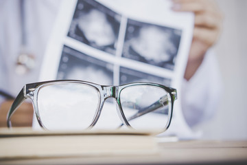 eye glasses on desk with blur background of doctor working in hospital office analyzing x-ray medical picture