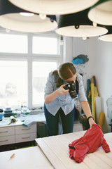 Woman Taking Photos Of Dog Clothes In Clothing Atelier
