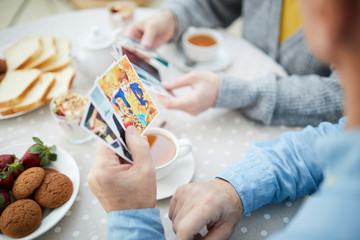 Hand of senior man holding photos of his grandson over served table with tea and desserts