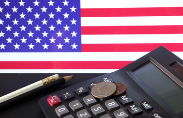 Coin of United stage of America on calculator and pencil on black floor with USA flag background, Quarter dollar and one cent or penny of USA money the concept of finance.