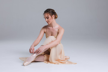 Enjoy your relaxation! Side view portrait of the young ballerina sitting on the floor in the modern dancing studio and posing at the camera.