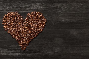 Coffee beans made in the heart shape form on black wooden surface background with copy space. Love of coffee concept.