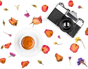Vintage retro photo camera, dried roses and coffee cup isolated on white background. Flat lay, top view