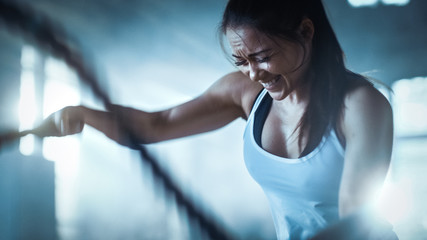Athletic Female in a Gym Exercises with Battle Ropes During Her Cross Fitness Workout/ High-Intensity Interval Training. She's Muscular and Sweaty, Gym is in Industrial Building.