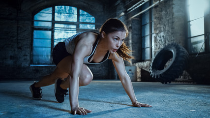 Athletic Beautiful Woman Does Running Plank as Part of Her Cross Fitness, Bodybuilding Gym Training Routine. Wall mural