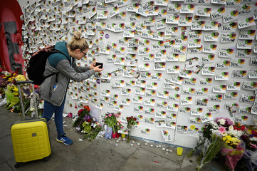 A woman takes a picture of messages and flowers are left at a memorial to Savita Halappanavar a day after an Abortion Referendum to liberalise abortion laws was passed by popular vote, in Dublin