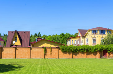 Beautiful country house with garage behind a brick fence.
