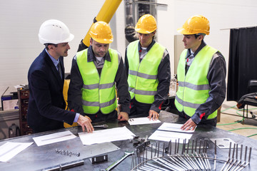 Engineer andworkers discuss papers