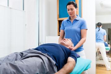 Elderly man getting massage from physio