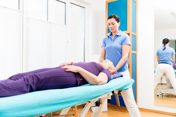 Elderly woman getting massage from physio