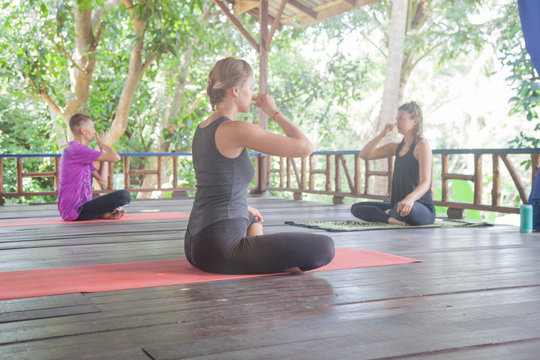 Young girls practicing yoga outdoors during yoga retreat vacation. Luxury yoga retreat.