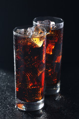 Glasses of cola with ice cubes on black stone