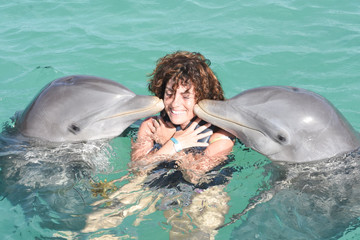Girl swimming with two Dolphin at dolfinarium water pool