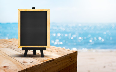 Blank blackboard on wood table food stand with blur sand beach and blue sea with bokeh light background.Template Mock up for summer vacation promotion sale.