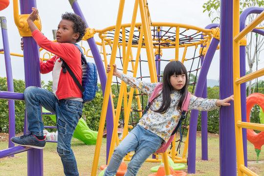 Two kids boy and girl having fun to play on children's climbing toy at school playground,back to school activity.kindergarten preschool.