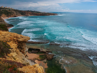Aerial view from a surf spot with waves and a group of surfers in Ribeira d' Ilhas beach in Ericeira, Portugal