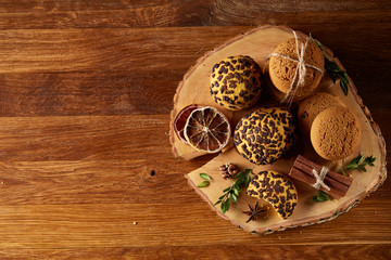 Sweet assortment of biscuits on a round wood log over rustic wooden background, close-up, selective focus.