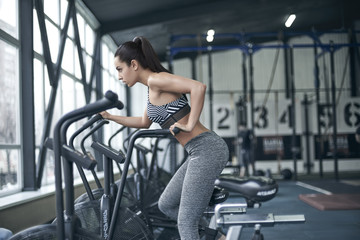 Young brunette woman doing cardio exercise in gym workout on bike concentrated close-up