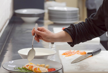 Hands of chef making ilast drops of sauce for italian sea-food carpaccio at kitchen of modern restaurant.