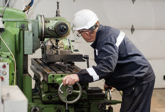 The old mechanic works at the lathe