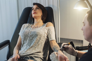 Woman listening to music while doing tattoo