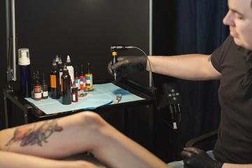 Professional tattoo artist making tattoo on leg