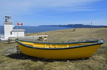 Bell Island lighthouse with a yellow dory boat in the foreground, Bell Island Avalon region Newfoundland Canada