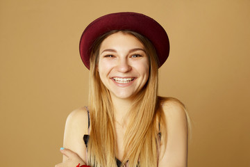 Beautiful young happy smiley woman posing in studio over yellow background