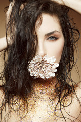 Attractive young woman with fashon make up with gold glitter on her neck over beige background
