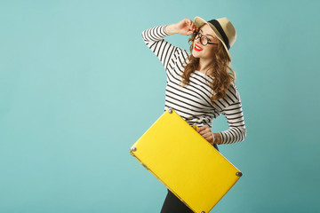Young happy beautiful woman in hat and funny toy glasses holding yellow suitcase over blue background