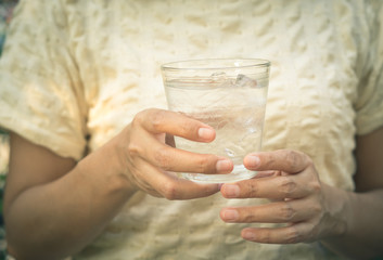 Woman hold glass of cold water.