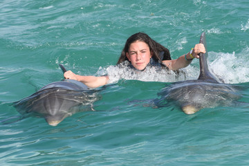 child girl swimming playing with dolphin on summer