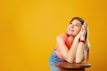Portrait of a beautiful happy young woman looking up on copy space over yellow background