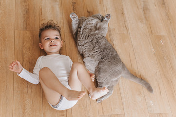 overhead view of adorable toddler boy and grey british shorthair cat lying on floor together at home