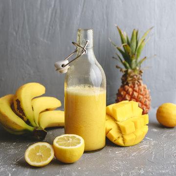 Refreshing yellow smoothie with lemons, banana, mango and pineapple on gray background