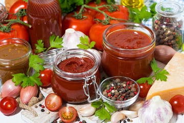 tomato sauces, pasta and fresh ingredients on wooden background