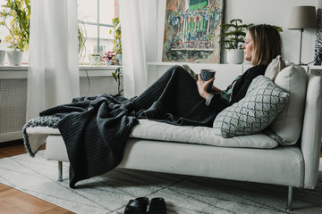 Young beautiful blonde swedish woman using her tablet at her comfortable home. Technology concept. Lifestyle photography.